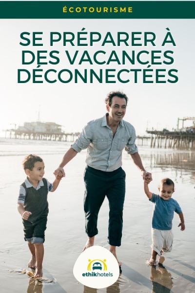 Un homme tient 2 enfants par la main sur une plage, ils sourient tous. derrière eux une jetée / un pear