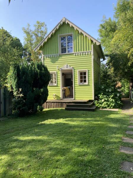 D'une ile a l'autre - cabane verte pomme avec un étage et devant une terrasse en bois