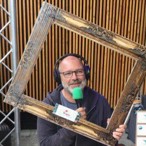 François Huet un micro à la main, un casque sur les oreilles qui pose avec un cadre de tableau autour de lui