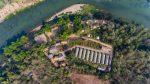 Photo prise du ciel de Namkhan Ecolodge parfaitement intégré dans son environnement dans le long d'un méandre du fleuve