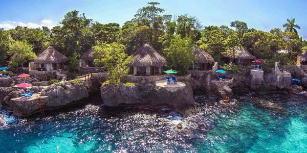 Photo prise depuis la mer, aux couleurs turquoises, des bungalows installés à flanc de rocher avec vue panoramique et terrasse et accès privé à la mer