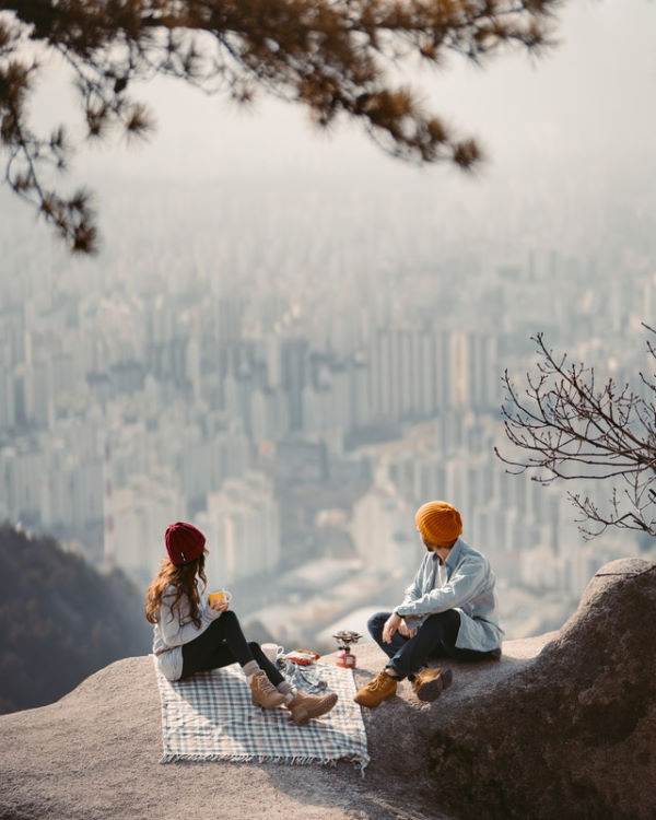 A couple picnicking on a cliff overlooking a city