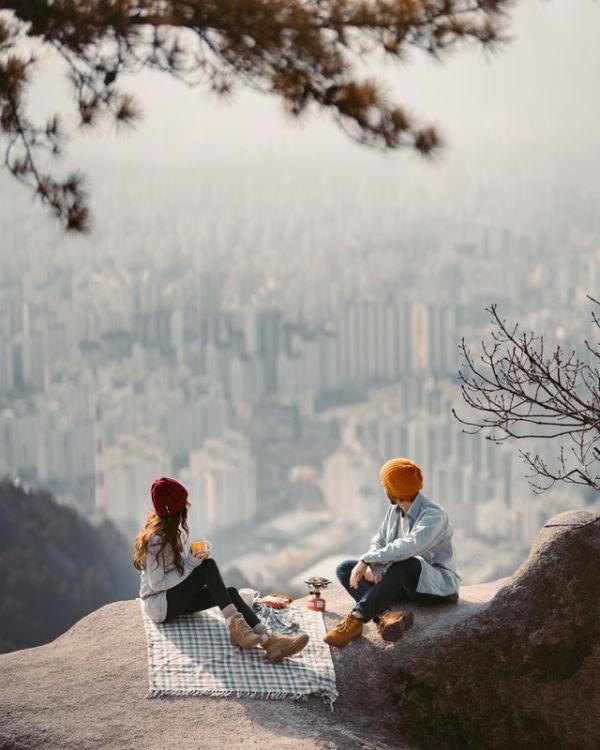 Nouvelles tendances du tourisme : Un couple en train de pique niquer sur une falaise surplombant une ville