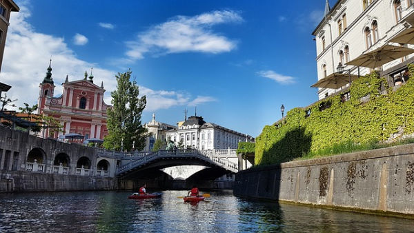 2 kayakers on a river in the city centre