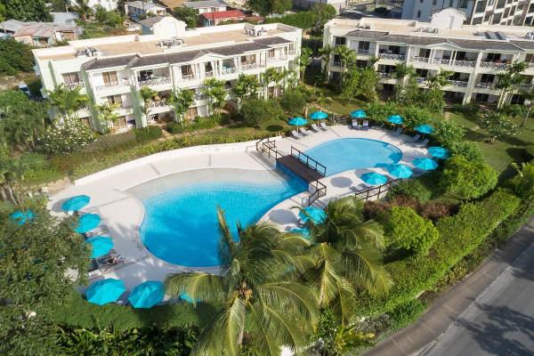Photo prise du ciel avec la piscine au centre, ses transats et parasol bleus autour et les batiments derrière