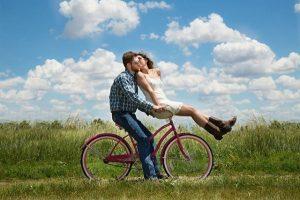 Couple sur un vélo rouge le long d'un champ fleuri. L'homme pédale et la femme est assise sur le guidon en l'embrassant