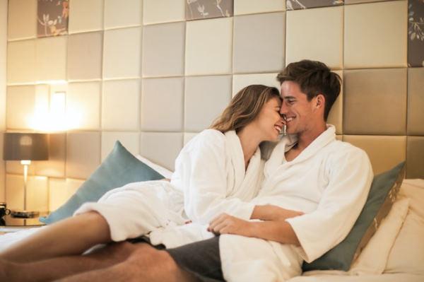 Séjour romantique : couple en peignoir s'enlaçant et souriant sur un lit