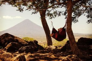 Une personne dans un hamac à l'ombre des arbres avec une vue spectaculaire sur une montagne