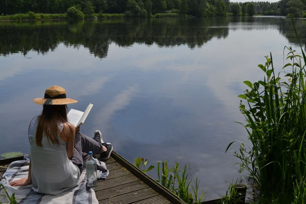 Disconnected holidays: woman with a hat sitting on a pontoon by the water reading a book