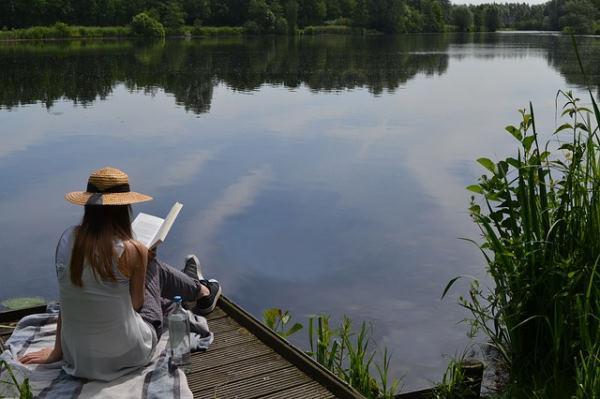 Vacances déconnectées : femme avec un chapeau assise sur un ponton au bord de l'eau entrain de lire un livre