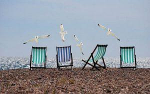 4 chiliennes rayées blanc et vert ou blanc et bleu sur une plage de cailloux face à la mer et avec des mouettes