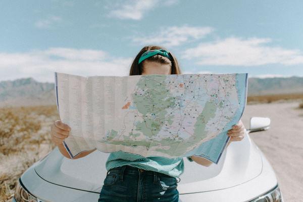 Préparer son road trip éco-responsable : femme appuyée sur le capot de sa voiture avec une carte routière depliée devant elle