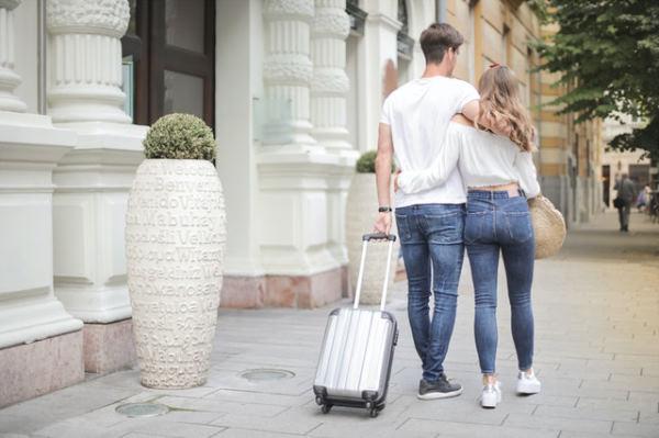 Un couple dans la rue habillés en jean et tee shirt blanc avec une petite valise cabine à roulette grise