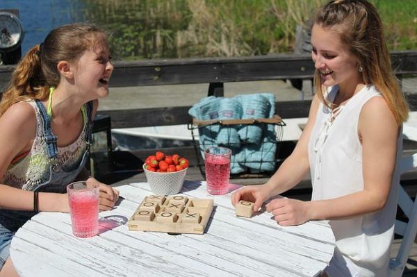 vacances déconnectées : 2 jeunes filles jouent au morpion sur une terrasse au soleil
