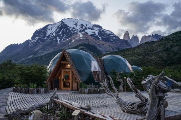 Igloos de couleur verte avec une porte en bois et posés sur une terrasse en bois. Derrière des montagnes enneigées