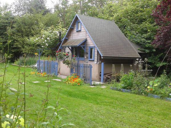 cabane grise avec des volet bleu au milieu d'une pelouse tres verte