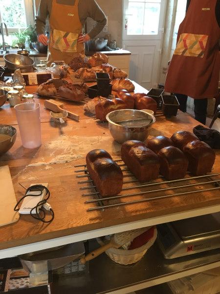 Photo de la table à la fin du cours de cuisine sur le pain au levain avec toutes les réalisations : pains et brioches