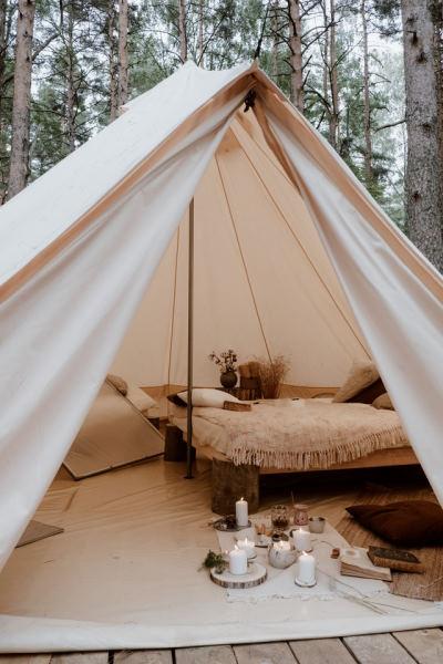 glamping en europe - intérieur d'une tente de glamping avec un tapis et un lit reposant sur des pieds en bois