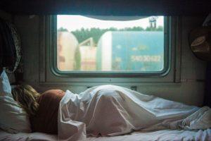 Femme couchée sur le côté de dos face à la fenetre enroulée dans un drap. Par la fenetre on voit un train de marchandise