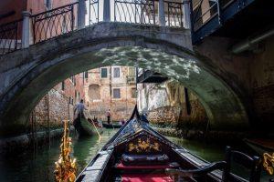 Photo prise d'une gondole qui passe sous un pont à venise. devant elle deux autres gondoles avec leur gondolier