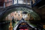 Photo taken from a gondola passing under a bridge in Venice. in front of her two other gondolas with their gondolier