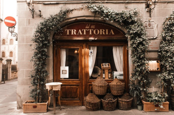 Preparing a road trip in Italy - Italian restaurant - Photo of a trattoria taken from the street with its wooden adventure and in front of wicker baskets