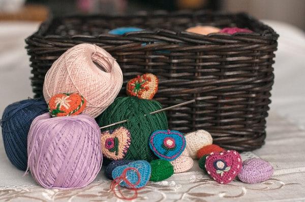 Pelotes de laine et de coton et des aiguilles posées devant un panier en osier avec également quelques éléments créatifs réalises