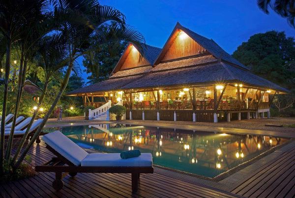 Photo prise de nuit au bord de la piscine avec au premier plan un transat en bois avec une serviette blanche roulée dessus, derrière la piscine et au fond un bâtiment de l'hôtel éclairé