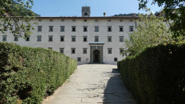 Escapade à Florence -L'entrée de l'Abbaye de Vallombrosa avec une allée longée de haie et emmenant vers un grand batiment blanc avec de nombreuses petites fenetres