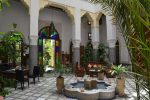 Patio traditionnelle d'un riad avec au centre une fontaine et autour des murs blancs avec un soubassement en mosaique comme sur le sol. Le bureau d'accueil y est installée dans l'angle gauche