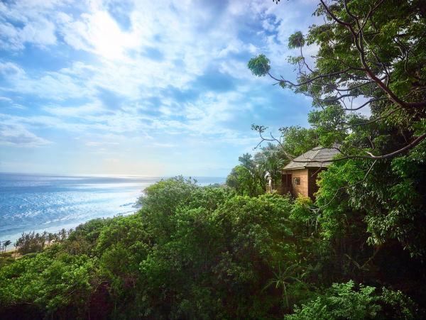 Bungalow en bois au milieu d'une forêt luxuriante avec une terrasse et une vue extraordinaire sur la mer