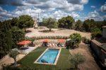 Photo prise avec un frome avec la piscine entourée d'herbe. Autour des transats et des parasols ouverts oranges. Au fond le moulin au milieu des oliviers
