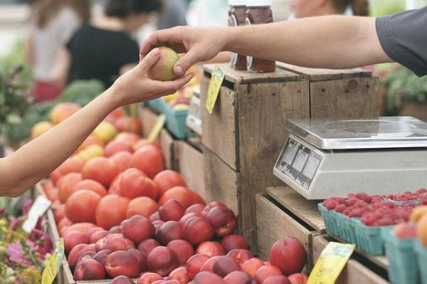 voyageur responsable - sur un marché au dessus d'un étal le vendeur donne un fruits à un acheteur
