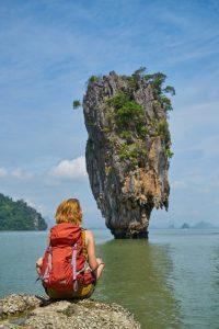 Femme assise entailleur par terre avec un sac à dos rouge dans le dos contemplant un éperon rocheux au milieu de la mer
